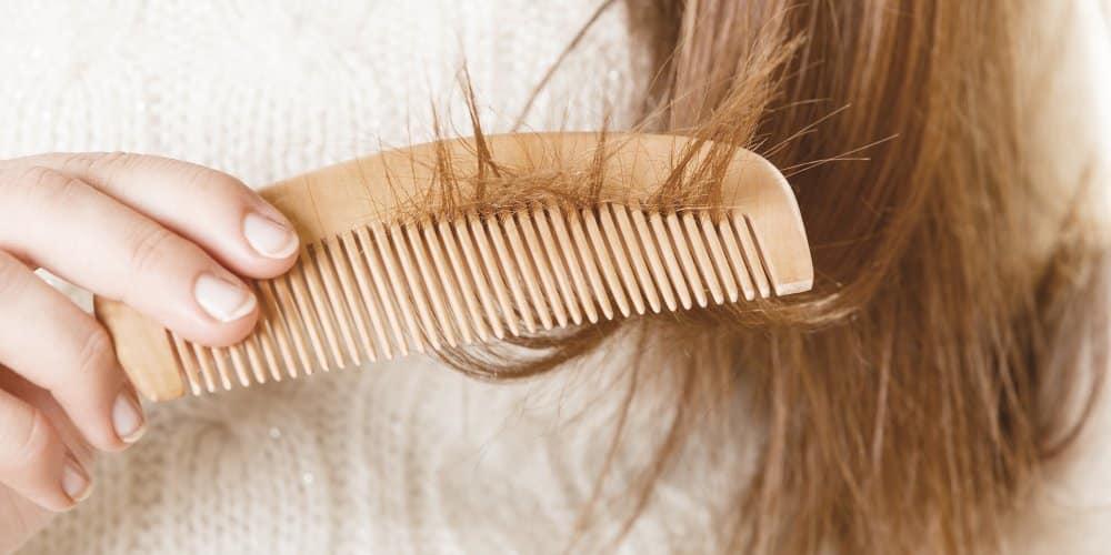 Une femme coiffant ses cheveux avec un peigne