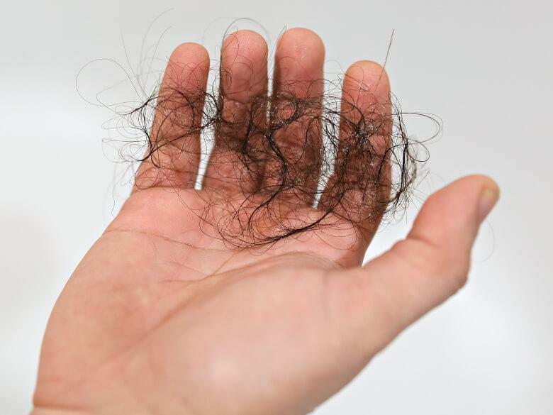 Personne tenant une poignée de cheveux dans ses mains